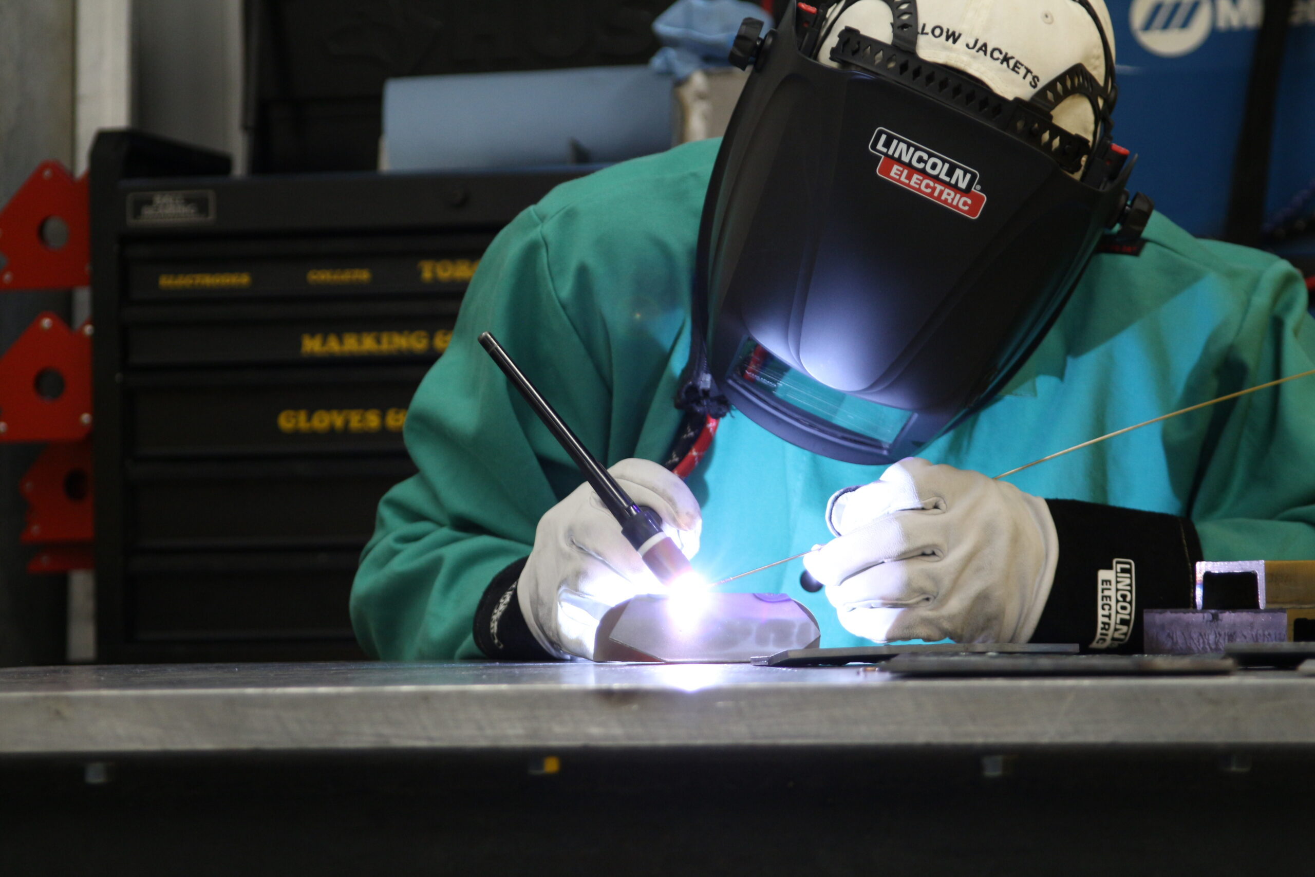 Shows a welding master actively welding using our MIG welder.